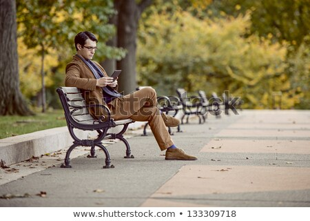 Handsome man with tablet in the park Stock photo © stockyimages