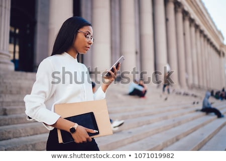 businesswoman with smartphone and folder at office Stock photo © dolgachov