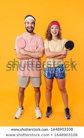 Portrait of athletic young couple holding rackets while playing  Stock photo © deandrobot