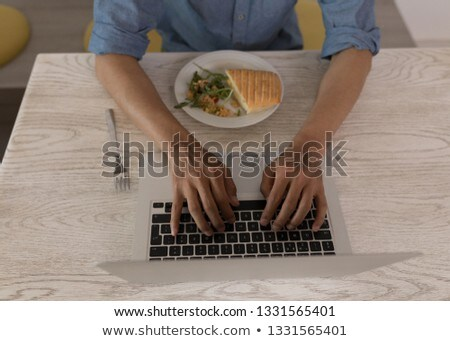 Mid section of young Asian male executive using laptop while eating lunch in modern office Stock photo © wavebreak_media