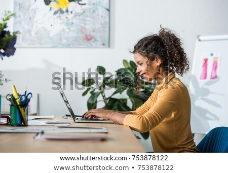 Side view of pretty young African American woman using digital tablet sitting on the beach hut. She  Stock photo © wavebreak_media