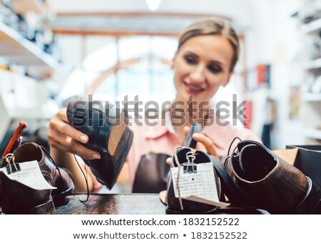 Woman shoemaker taking shoes to be repaired off the shelf Stock photo © Kzenon