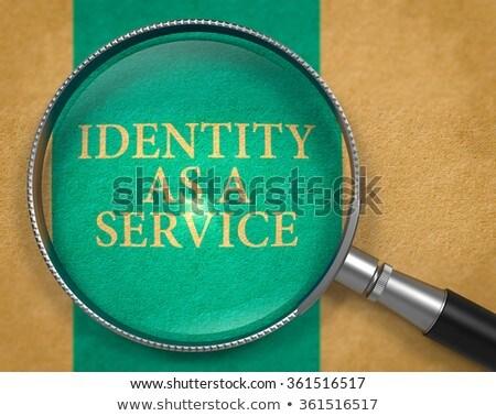 Identity-as-a-Service through Loupe on Old Paper. Stock photo © tashatuvango