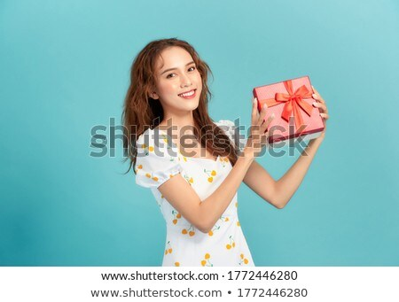 Excited asian beautiful woman isolated over blue background eat chocolate. Stock photo © deandrobot