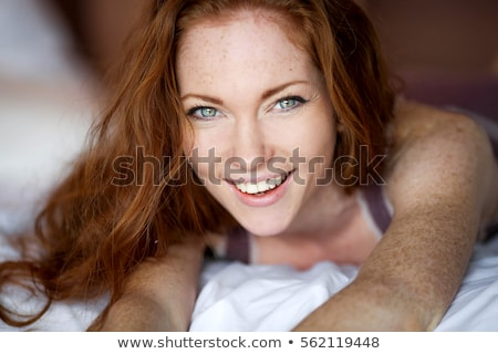 Morning in bed, a young charming red-haired woman with freckles lying in bed, hugging pillow, smilin Stock photo © ElenaBatkova