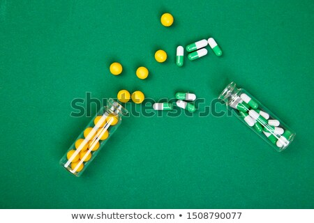 Stock photo: Flat lay overhead of yellow and green pills in glass jar on paper background