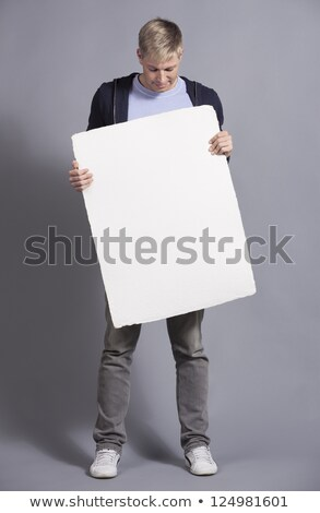 Joyful likable man showing empty signboard. Stock photo © lichtmeister
