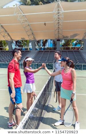 Cuatro jóvenes tenis jugadores manos junto Foto stock © Kzenon