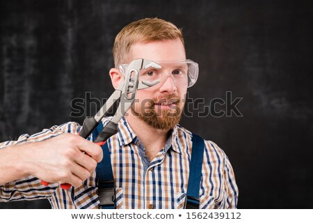 Happy young bearded mechanic in protective eyewear showing new handtool Stock photo © pressmaster