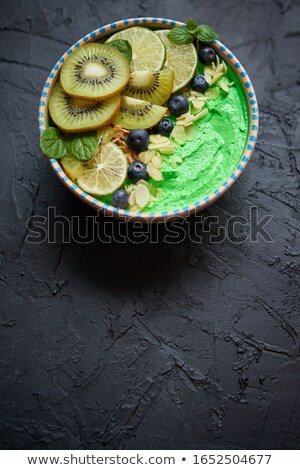 Stockfoto: Green Smoothie Or Yogurt Bowl With Fresh Kiwi Blueberries Lime And Almond Flakes