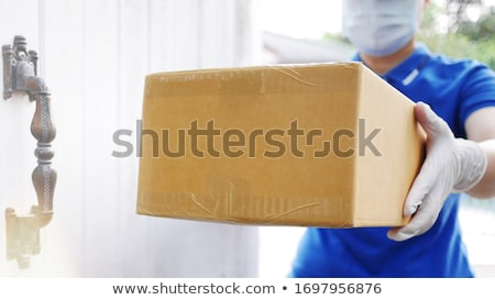 Stock fotó: Courier Delivery Man In Protective Mask And Medical Gloves During The Coronavirus Epidemic