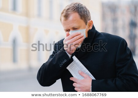 Sick man coughs, covers mouth with palm, wears medical mask, has symptoms of allergy, flu, influenza Stock photo © vkstudio