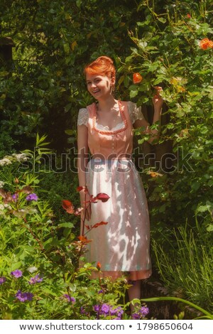 standing young redhead woman in bavarian dress stock photo © rob_stark