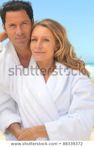 Couple embracing by the sea in toweling robes Stock photo © photography33