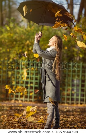 Stock fotó: Happy Woman With Umbrella And Falling Yellow Leaves