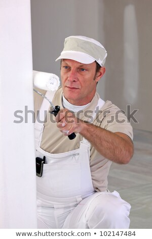 squatting tradesman painting a wall stock photo © photography33