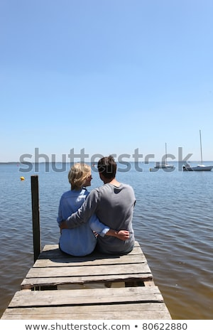 Couple sitting on the end of a pontoon with their arms around each other Stock photo © photography33