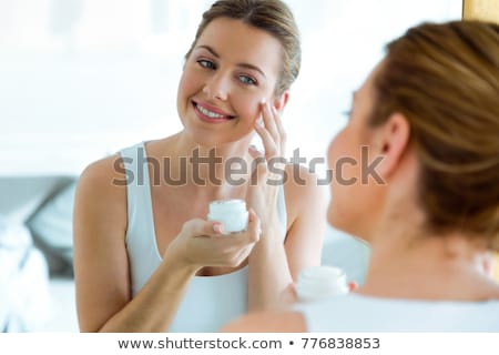 Portrait of the beautiful young blonde near a mirror stock photo © acidgrey