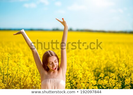 Beautiful young woman relaxing in a colza field  Stock photo © Geribody