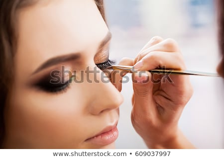 pretty woman applying make up close up stock photo © kurhan