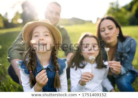 Stock photo: Young beautiful woman blowing a dandelion in spring scenery