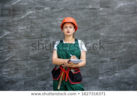 pretty girl in tool belt holding white helmet and hammer stock photo © cherezoff