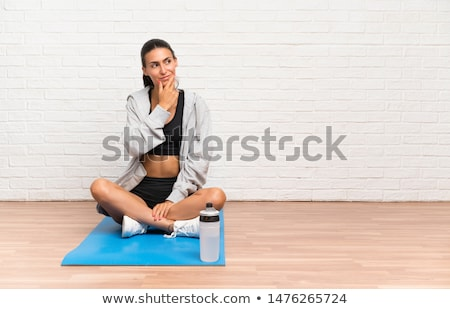 Stock photo: Young thoughtful fit woman sitting on the floor at gym