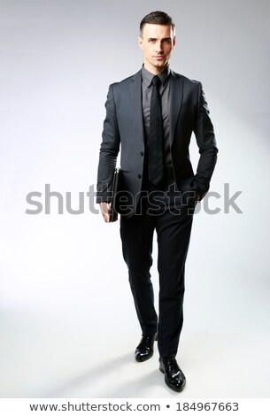 Full-length portrait of a pensive businessman standing with laptop on gray background Stock photo © deandrobot