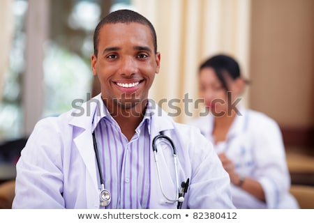 Stock photo: Smiling african-american doctor making with colleagues behind