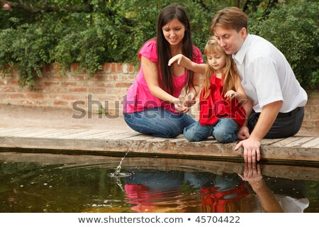 Little girl in red dress throws stones in water together with parents. stock photo © Paha_L