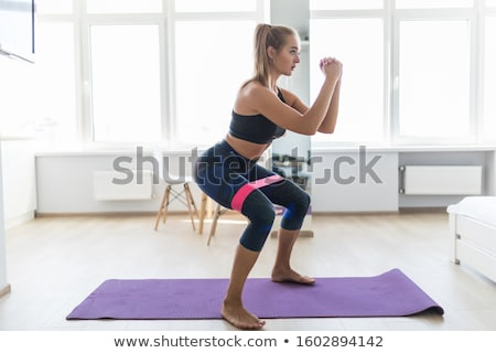 Beautiful woman doing sport exercise with rubber Stock photo © svetography
