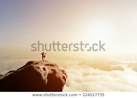 asian man fighter practices martial arts in high mountains above clouds stock photo © photocreo
