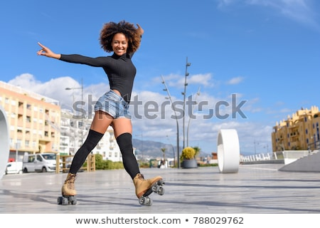 cheerful young woman riding on roller skates outdoors stock photo © deandrobot