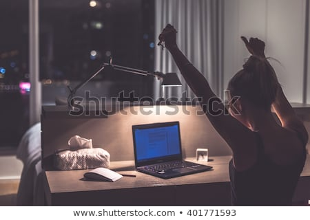 young woman working on her laptop late at night stock photo © lightpoet