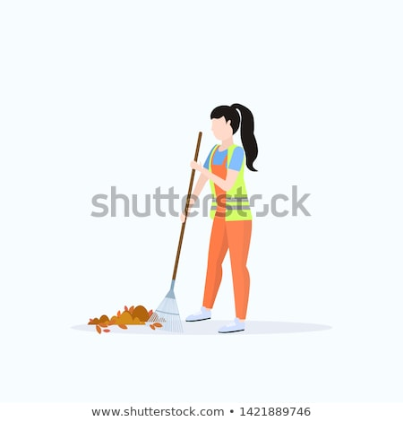 Smiling woman raking leaves outdoors Stock photo © IS2