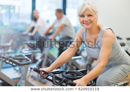 young woman on exercise bike stock photo © is2