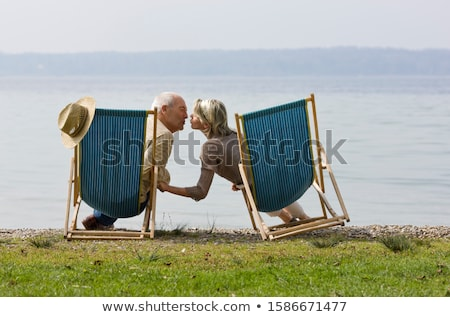 Stock photo: Couple relaxing in deckchairs rear view