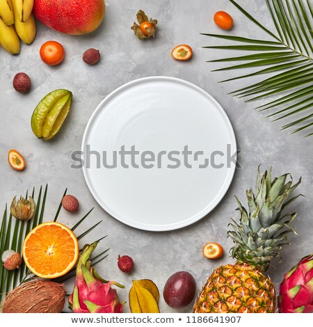 Composition from an empty white plate of green palm leaves, pineapple, mango and passion fruit on a  Stock photo © artjazz