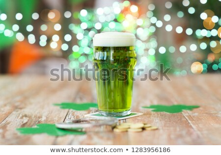 glass of beer, shamrock and coins on wooden table Stock photo © dolgachov