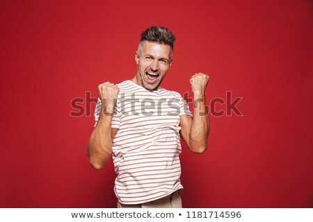European man in striped t-shirt screaming and clenching fists, i Stock photo © deandrobot