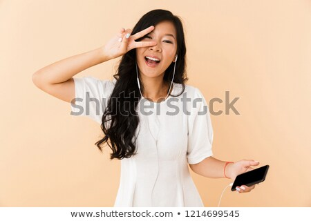 Happy asian woman posing isolated over beige wall background listening music with earphones by phone Stock photo © deandrobot