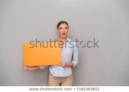 Shocked business woman standing over grey wall background holding speech bubble. Stock photo © deandrobot