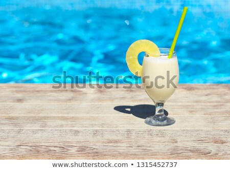 Glass of pinacolada cocktail standing on the swimming pool ledge Stock photo © dashapetrenko