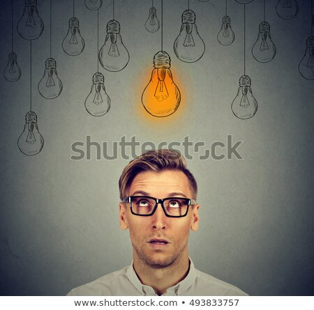 business man with thoughtful expression looking at bright light bulb stock photo © ichiosea