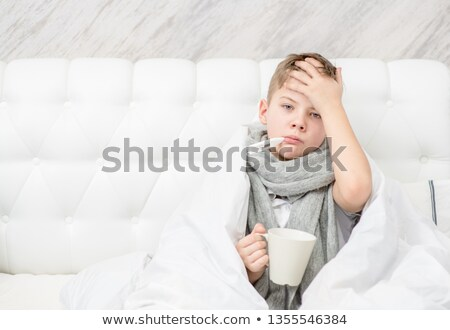 Sick boy drinking tea in his bed. Sick child with fever and illness in bed Stock photo © galitskaya