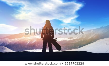 Silhouette of a snowboarder on a background of sunlit snowy mountains. Stock photo © ConceptCafe