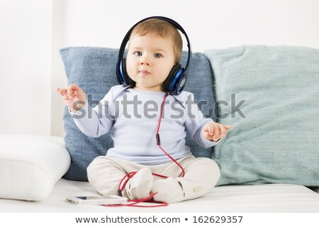 Baby boy listening music at earphones with iphone in hands. Stock photo © lichtmeister
