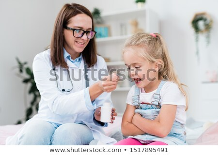 sick little girl taking medicine from spoon held by young female doctor stock photo © pressmaster