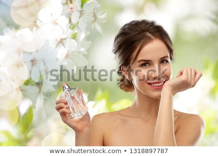 happy woman with perfume over gray background Stock photo © dolgachov