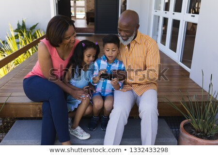 Front view of multi-generation African American family reviewing photo on mobile phone on the porch  Stock photo © wavebreak_media